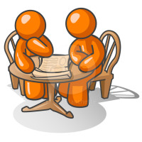 Two orange men at a wooden table pondering a problem together.